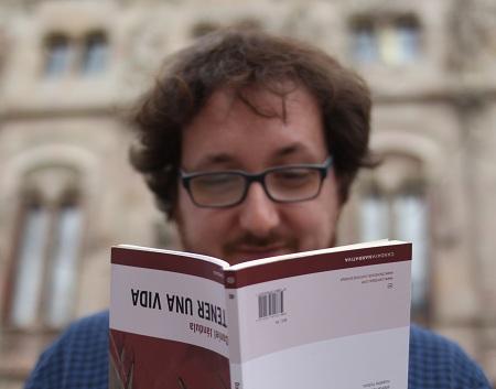 Jándula sosteniendo, al revés, un ejemplar de Tener una vida. / J.Soriano