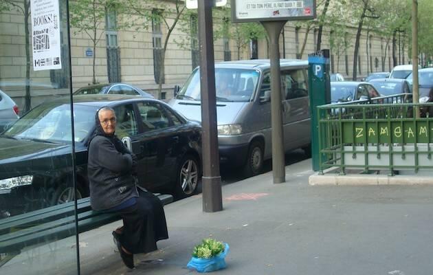 Una anciana espera en un para de bus en París. / Jacqueline Alencar, 2011,