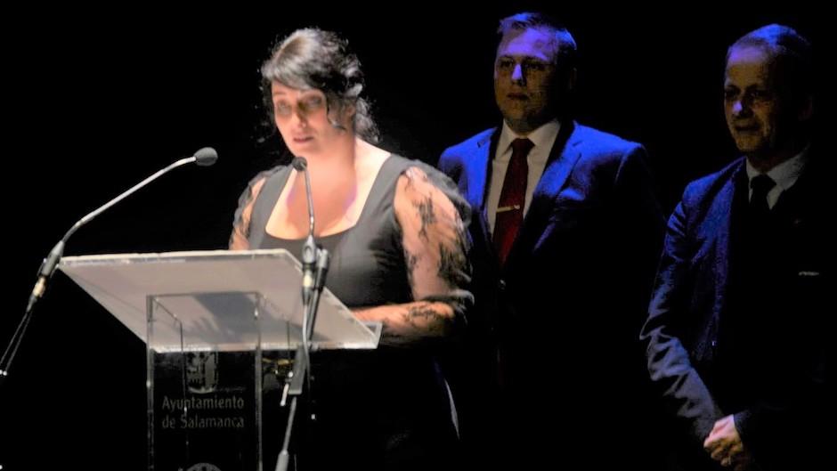 Laura García de Lucas, ganadora de la primera edición,  leyendo en el Teatro Liceo de Salamanca. Atrás Andy Wickham y Luis Fajardo./ de José Amador Martín.,
